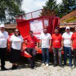 L'équipe de la soupe populaire de Novo Brdo et les volontaires de Solidarité Kosovo devant une arracheuse de maïs offerte par l'association.